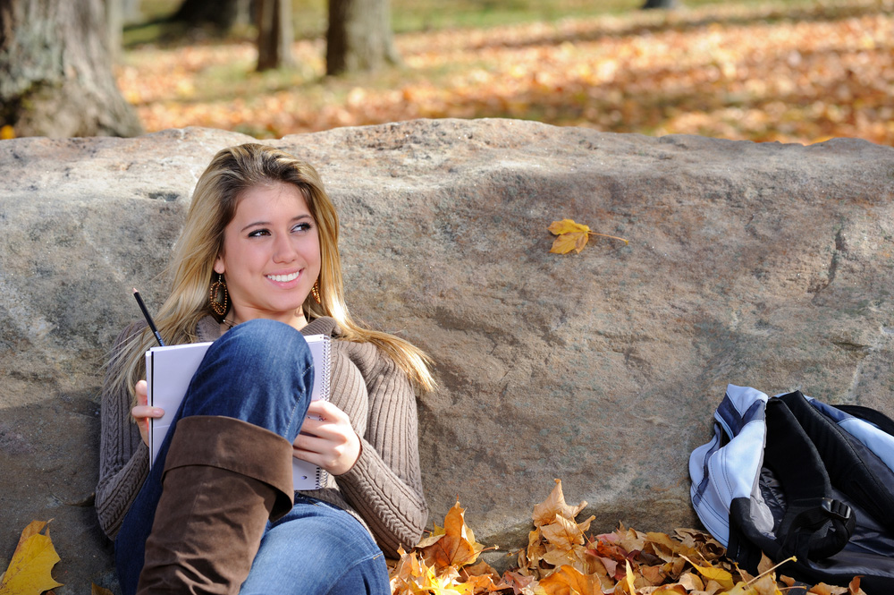 Female student studying outside in the fall