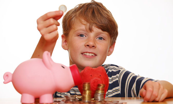 Boy putting change in his piggy bank