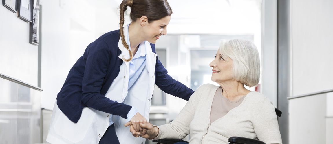 Nurse with elderly woman in long term care facility