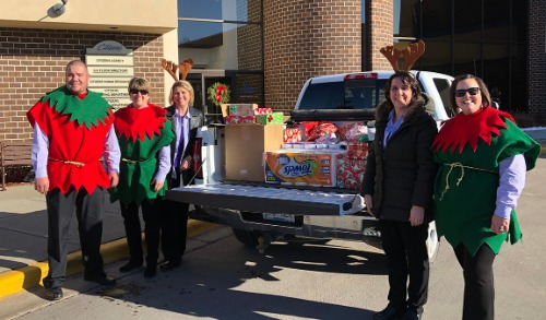 Group dressed as elves and reindeer in front of truck filled with donation items