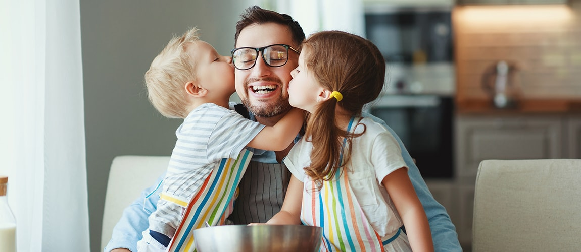 Two children kissing their father on the cheek