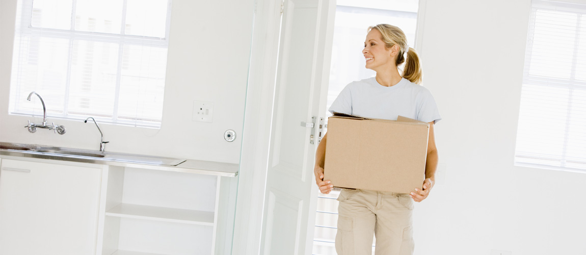 Lady walking into home with moving box