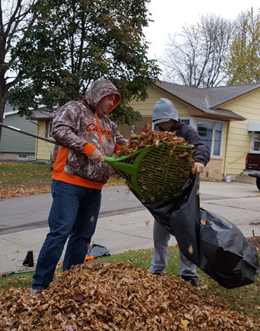Citizens employee and son helping rake leaves for Day of Caring